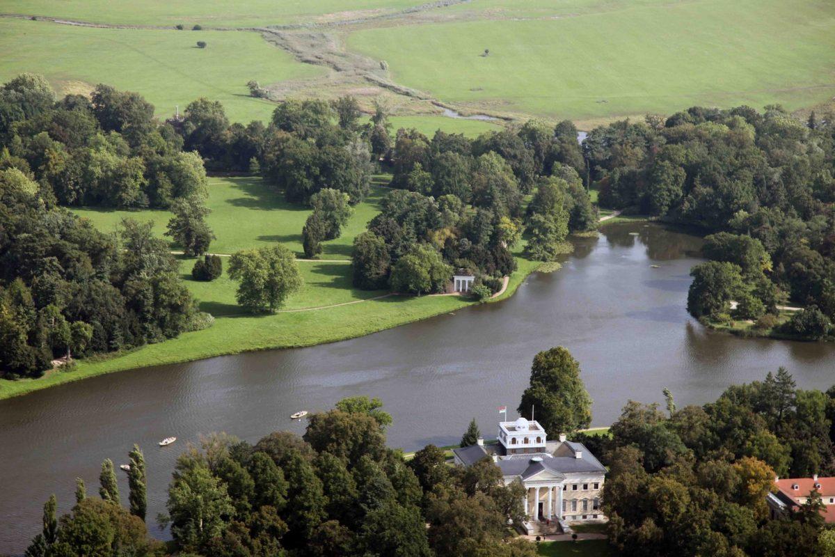 Das weite Bild vom Wörlitzer Schloss zeigt den über den Außendeich hinaus zu den Seen und Flutrinnen der Elbe