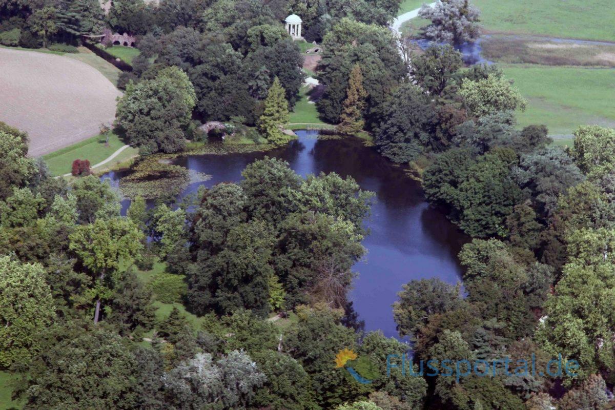 Der Floratempel hoch oben auf dem Deich dominiert mit seiner schönen Sichtachse den See. Links davon sieht man die die lange Linie des Kettenbrückenkanals.