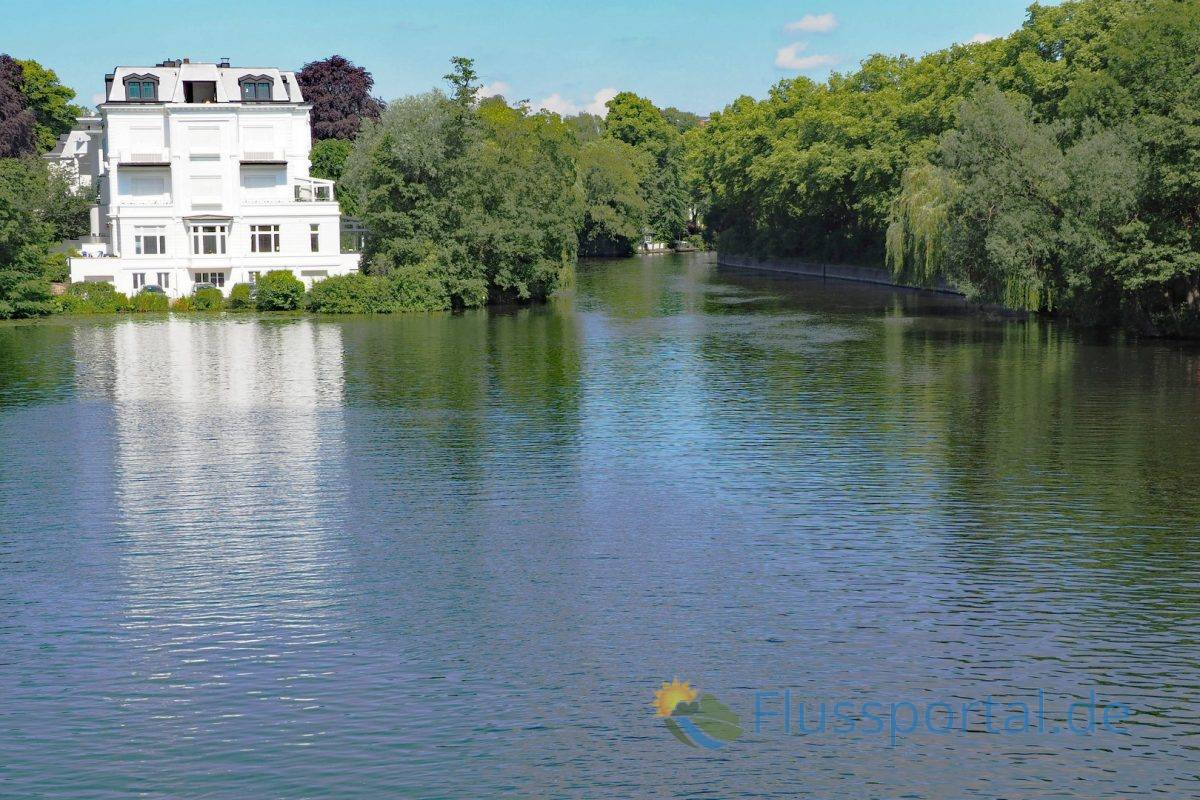 Die die schöne weiße Villa an der Heilwigstraße liegt vor einer großen Bucht des Alsterkanals