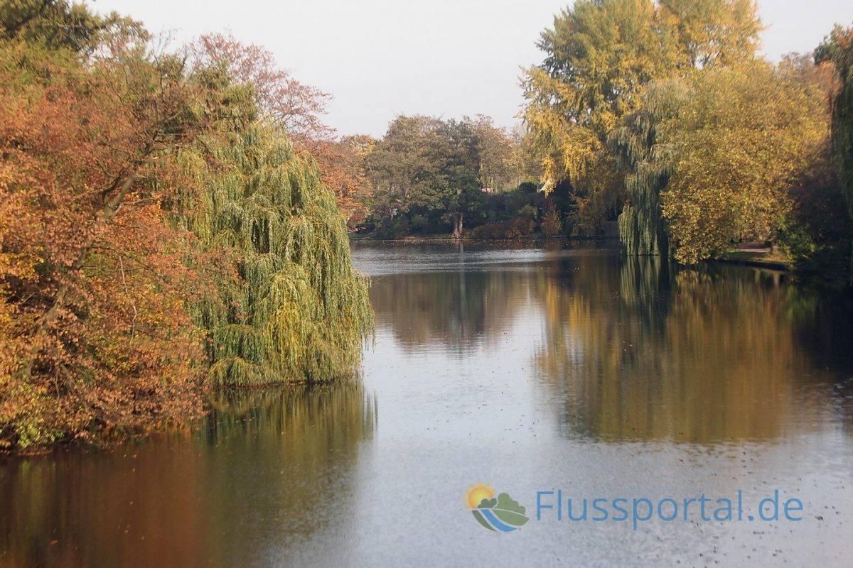 Das Foto von der Deelbögebrücke zeigt die Grünflächen am Alsterkanal von dem der Inselkanal-links im Bild -abzweigt